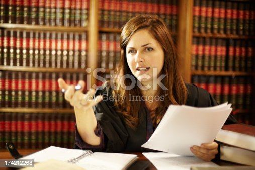 Attractive young judge sitting at her desk discussing the law