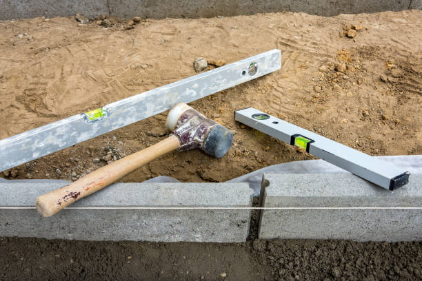 Setting edge restraints with border stones in concrete and level and mallet stock photo