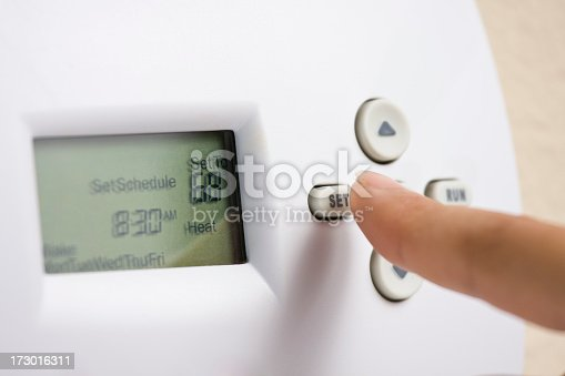 Female hand setting thermostat to 68 degrees Fahrenheit to save energy in the winter.