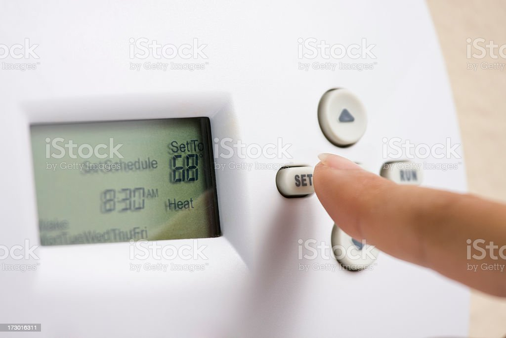 Setting electronic thermostat heat to 68 degrees stock photo