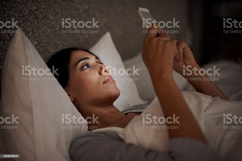 Setting her alarm for an early wake up stock photo