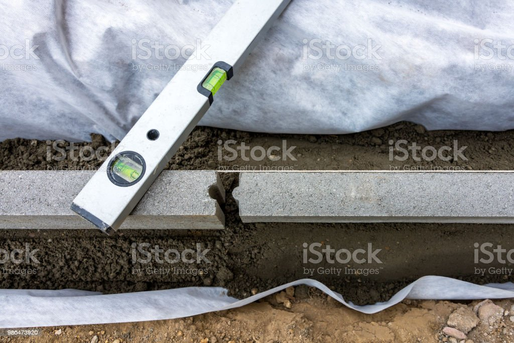 Setting of edge restraints with border stones in concrete with bubble level stock photo