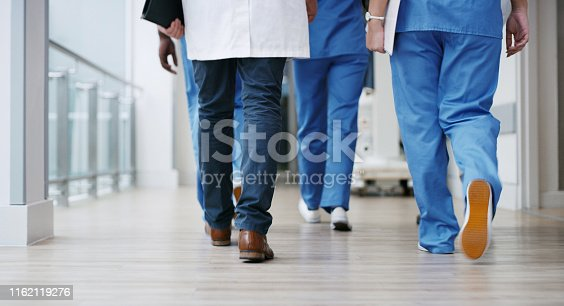 Closeup shot of a group of unrecognisable doctors walking in a hospital