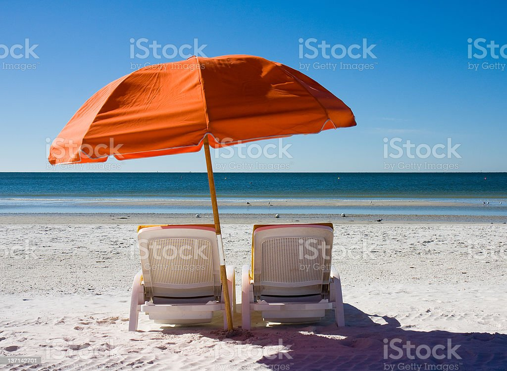 A setting on the beach of beach chairs and an umbrella  royalty-free stock photo