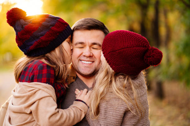 setting sun. daughter kiss dad on cheek. concept of happy family. the setting sun. daughter kiss dad on the cheek. the concept of a happy family. little girl kissing dad on cheek stock pictures, royalty-free photos & images