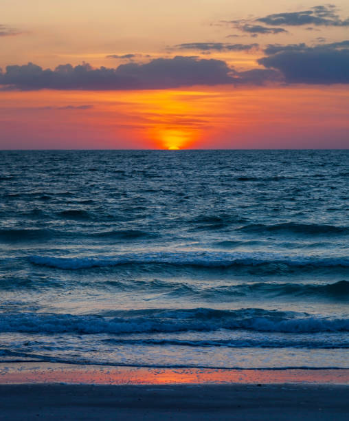 Setting sun exactly at the horizon on the Gulf of Mexico at Clearwater Beach Florida