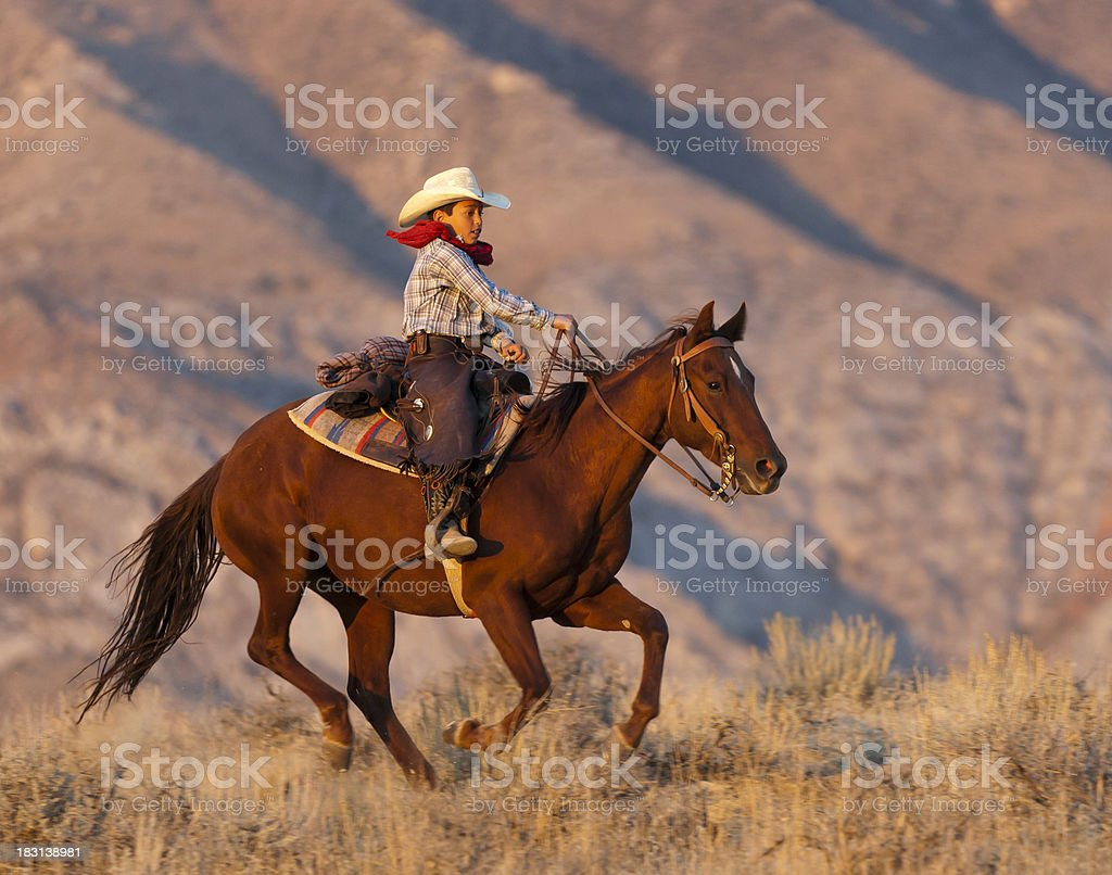 Puesta de sol ilumina galloping horse and young boy rider - foto de stock