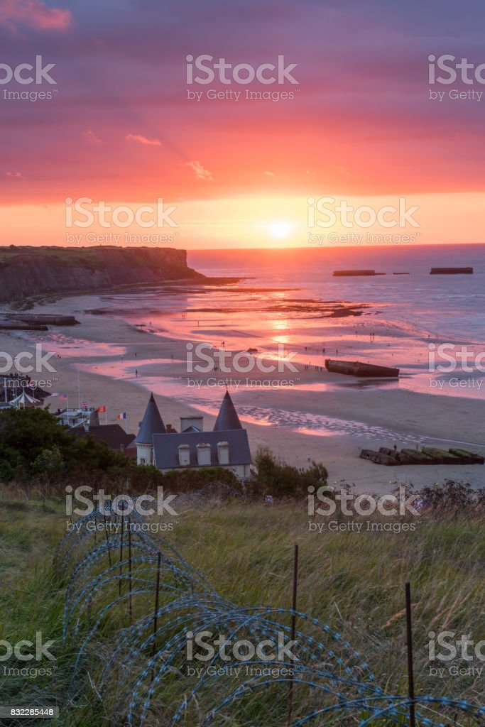 Setting sun on Mulberry Harbours at Arromanche stock photo