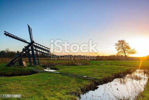 Setting sun over a windmill in the Weerribben-Wieden nature reserve in Overijssel, The Netherlands.