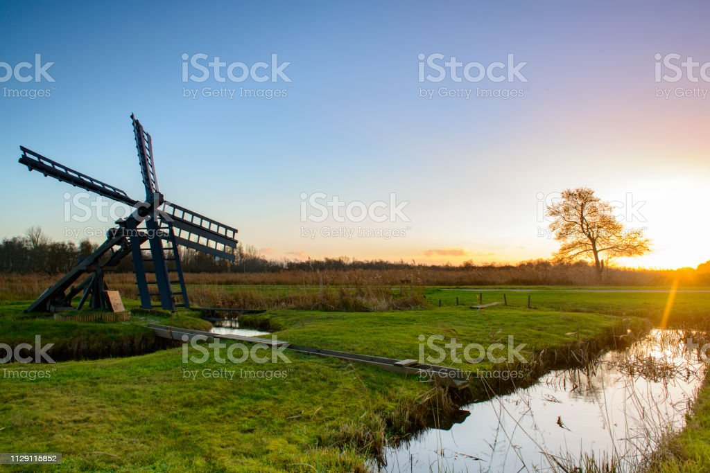 Setting sun over a windmill in the Weerribben-Wieden nature reserve in Overijssel, The Netherlands. stock photo