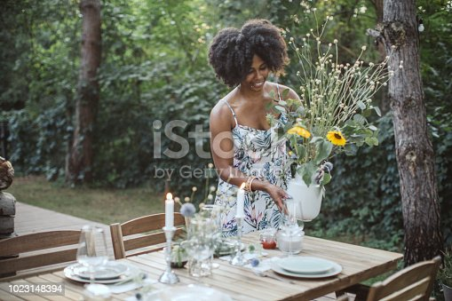 Woman preparing dinner table in backyard of the cottage. She enjoy in countryside nature and vacation