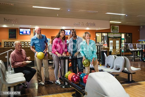 Six senior people are setting up the tenpin bowling scoreboard, one is preparing to bowl.