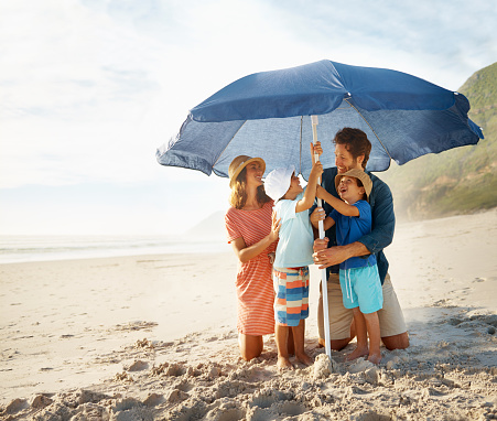 Shot of a happy young family setting up a beach umbrellahttp://195.154.178.81/DATA/i_collage/pu/shoots/784348.jpg