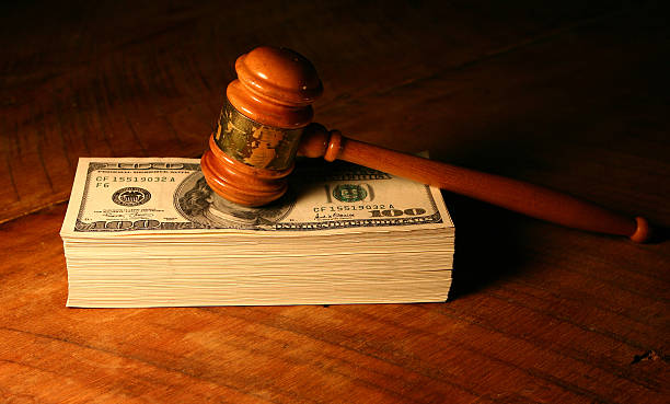 Settle out of Court Used gavel on a stack of money. lawsuit stock pictures, royalty-free photos & images