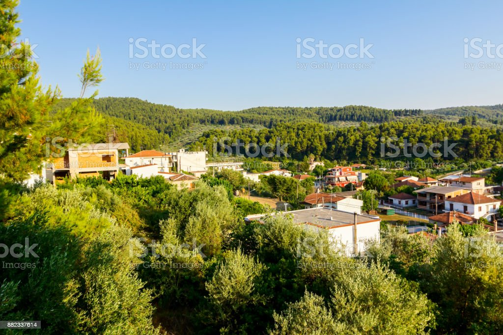 Settlement among hilly ground with confiner forest stock photo