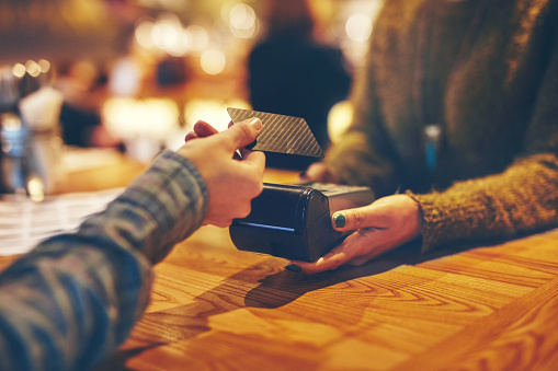 Closeup shot of a customer making a credit card payment in a cafe