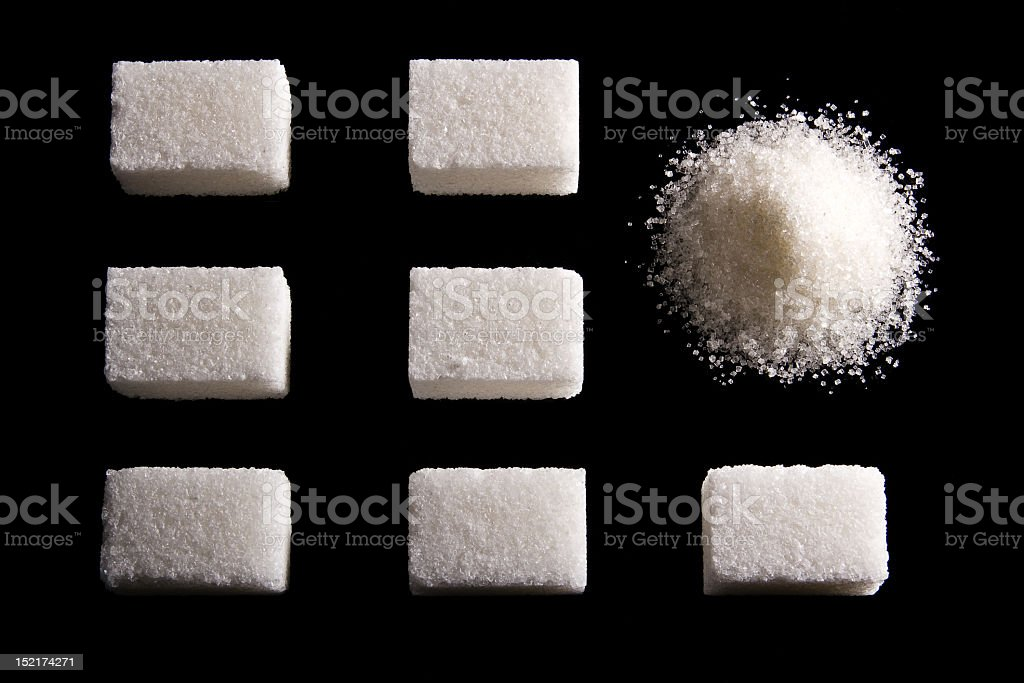 Seven blocks of sugar and one small pile of ground sugar  royalty-free stock photo