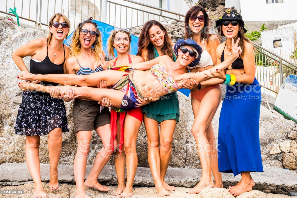 seven caucasian females friends people group enjoy and play together in summer dress for vacation and friendship concept. sunlight and colored image with women smile and enjoy relationship outdoor stock photo
