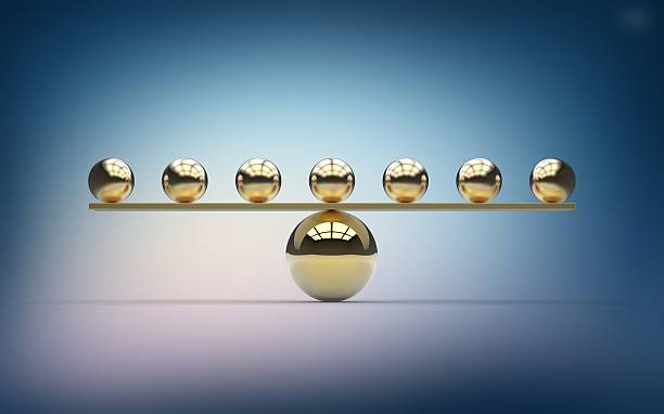 seven gold balls balancing on one large gold ball - solid stock photos and pictures