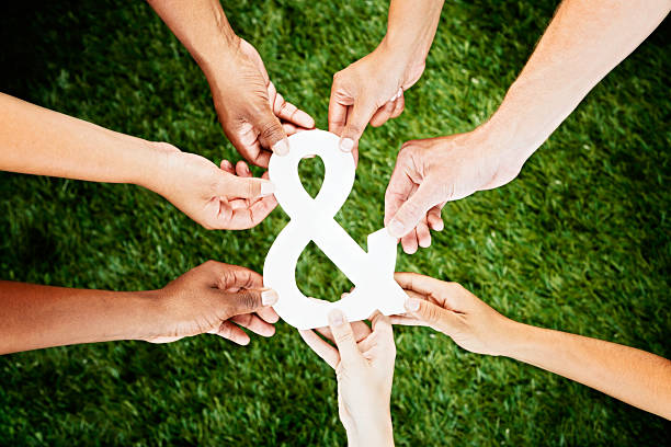seven hands reaching for & sign - ampersand stock pictures, royalty-free photos & images