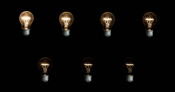 Seven lightbulbs on black background stock photo