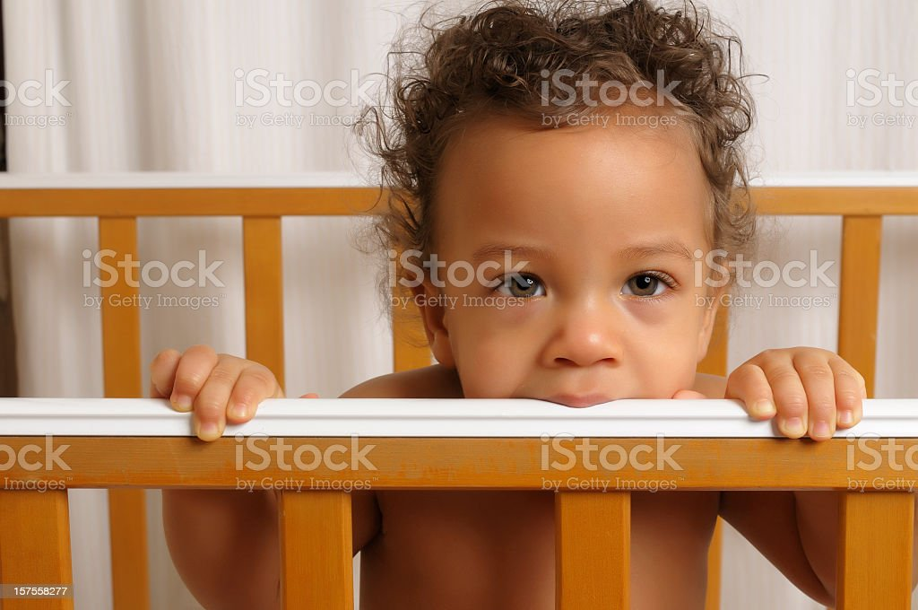 Seven month old baby standing in his cot royalty-free stock photo