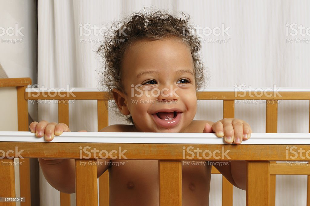 Seven month old baby standing in his cot stock photo