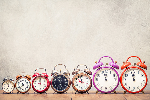 istock Seven retro alarm clocks with last minutes to twelve o'clock on wooden table front concrete wall background. Vintage old style filtered photo 1055677726