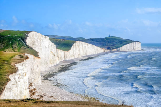 seven sisters country park tall white chalk cliffs, east sussex, UK, Seven Sisters cliffs, tall white chalk cliffs with the sea infront and on top of the cliffs is grass above a blue sky, at the bottom of the nearest cliff is a big pile of chalk from a recent cliff fall of eroded rock, southeast england stock pictures, royalty-free photos & images