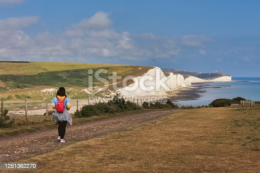 A tourist walks there on the magnificent white cliffs known as Seven Sisters at low tide, Eastbourne, East Sussex, England.