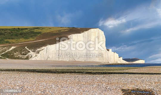 Eastbourne, England - July 20, 2020: A tourist walks there on the magnificent white cliffs known as Seven Sisters at low tide, Eastbourne, East Sussex, England.  Square panoramic.