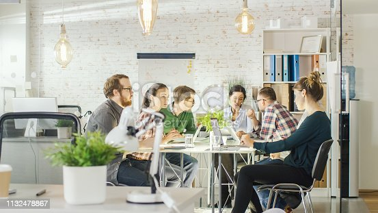 Seven Stylish People Having Planning Business Session Sitting at Big Table in their Bright Modern Creative Office.