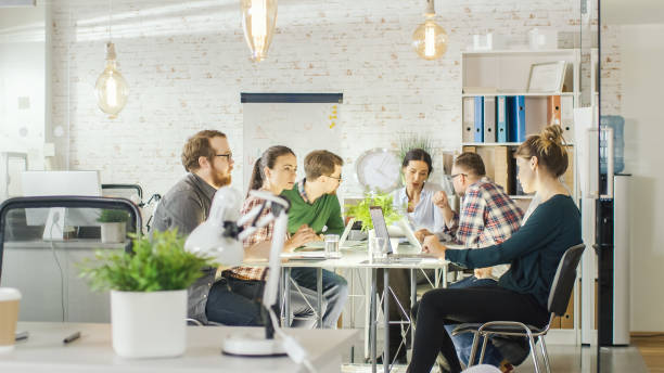 seven stylish people having planning business session sitting at big table in their bright modern creative office. - imobiliaria imagens e fotografias de stock