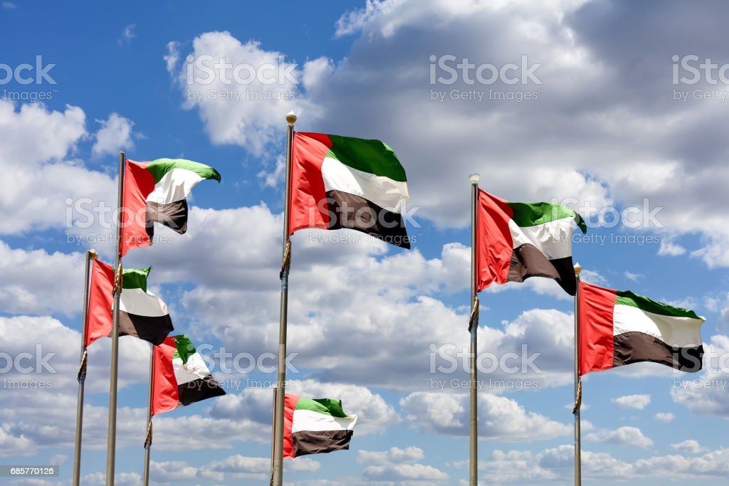Seven United Arab Emirates flags against blue sky with clouds. - 免版稅7號圖庫照片
