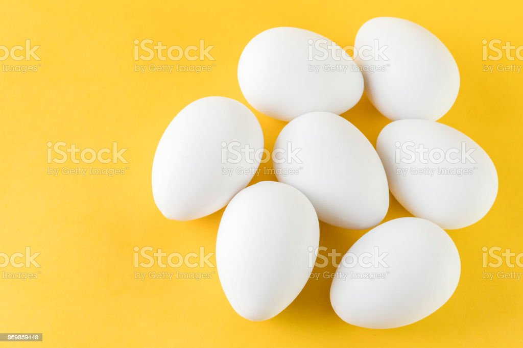 Seven White Hen Eggs Isolated On Yellow Background stock photo
