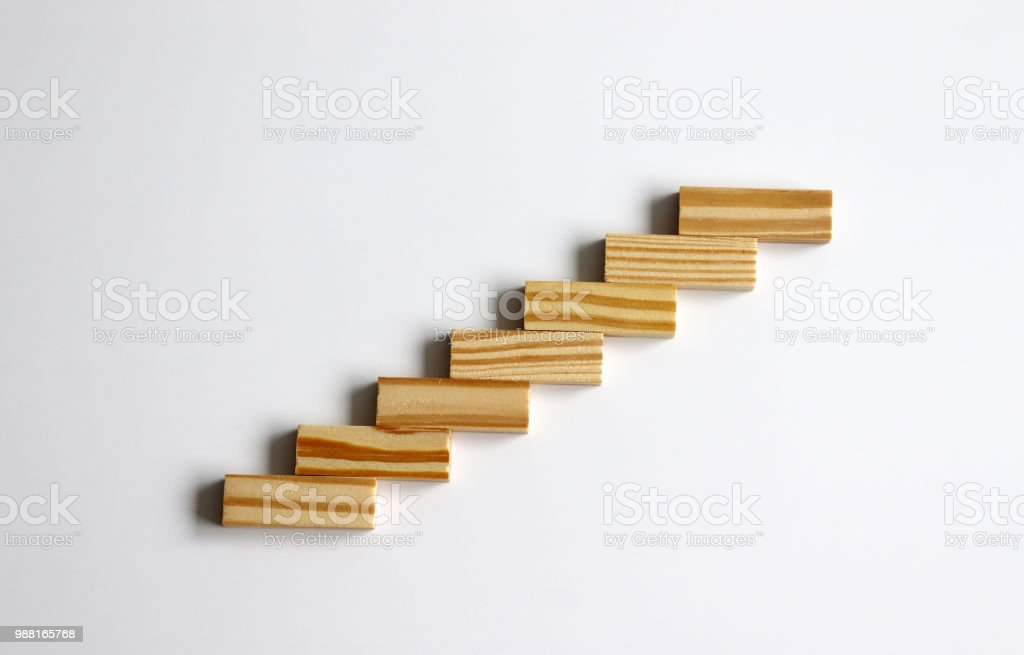 Seven wooden blocks stacked in the shape of a staircase. stock photo