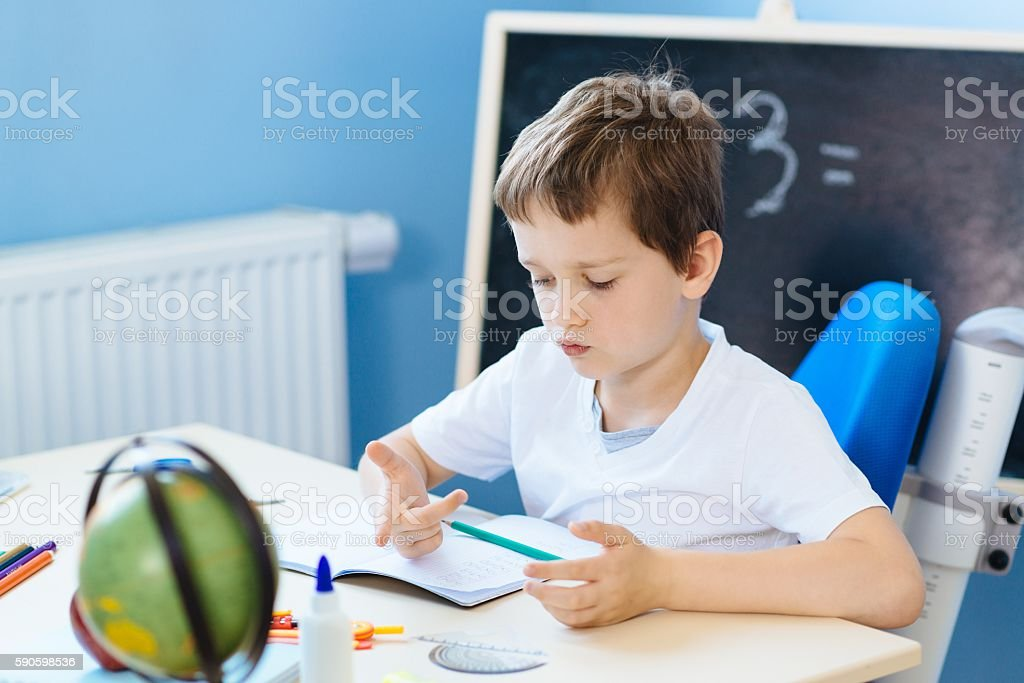 Seven years old boy, counting on fingers stock photo
