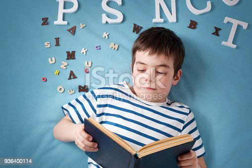 istock seven years old child lying with book and letters 936400114