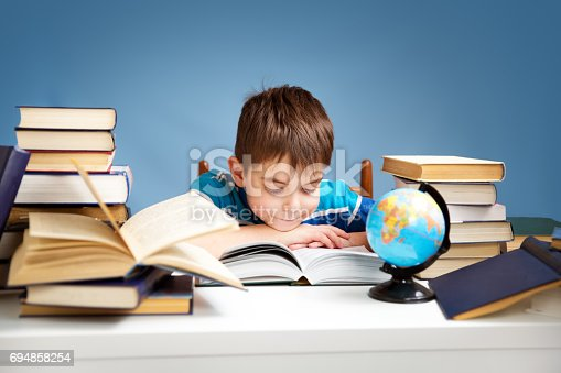 683105722 istock photo seven years old child reading a book 694858254
