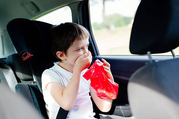 Seven years old child vomiting in car stock photo