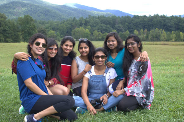 Seven Young Asian - Indian women posing in a field in front of the Smokey Mountains stock photo