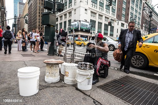 New York City, USA - July 25, 2018: Drummer man playing from plastic pots like a drum on Seventh Avenue (7th Avenue) while a man in a suit comes out of a taxi and people around in Manhattan in New York City, USA