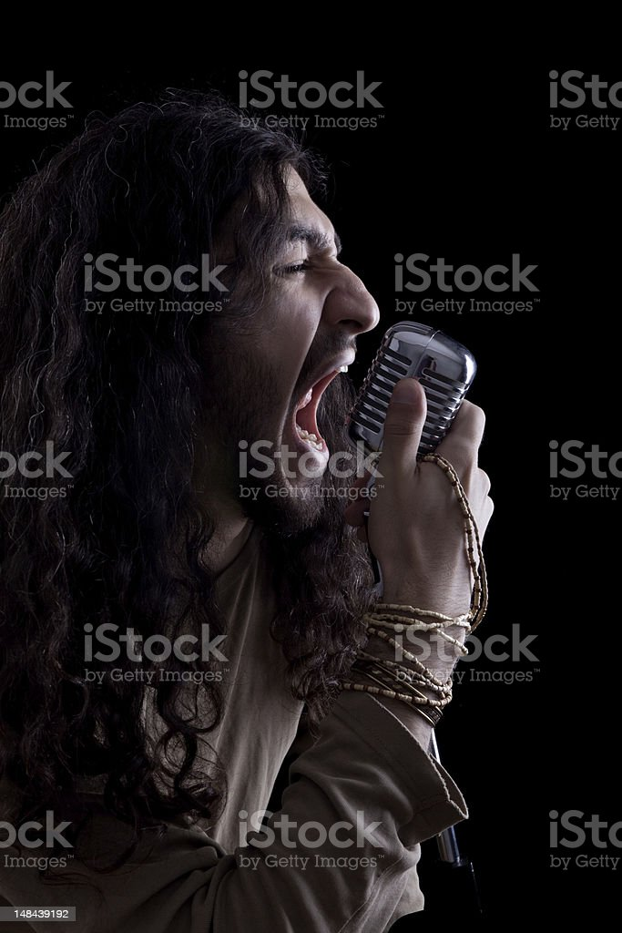 Seventies rock star singing on old fashioned microphone royalty-free stock photo