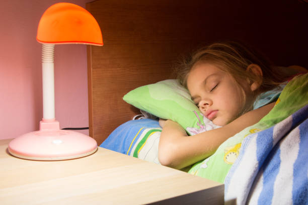 Seven-year girl asleep in bed, reading lamp is included on the next table stock photo