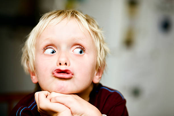 Seven-year-old boy rolls his eyes to the right Wide eyed, a boy grimaces as he looks to the right of frame, right where you can add your message. Shot with Canon EOS 1Ds Mark III. grimacing stock pictures, royalty-free photos & images