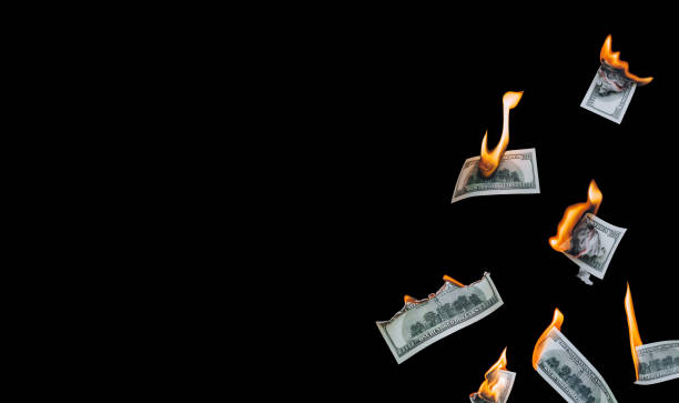 Several 100 dollar bills, falling down, burn on a black background. The concept of bankruptcy, depreciation, devaluation, wastefulness and waste of money. Copy space, isolated. Several 100 dollar bills, falling down, burn on a black background. The concept of bankruptcy, depreciation, devaluation, wastefulness and waste of money. Copy space, isolated. depreciation stock pictures, royalty-free photos & images