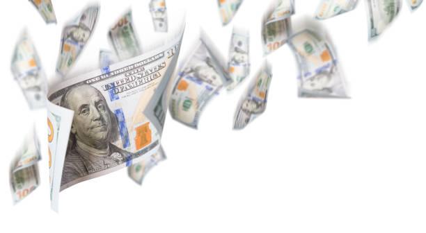 Mehrere 100-Dollar-Scheine fallen von oben auf weißem Hintergrund – Foto