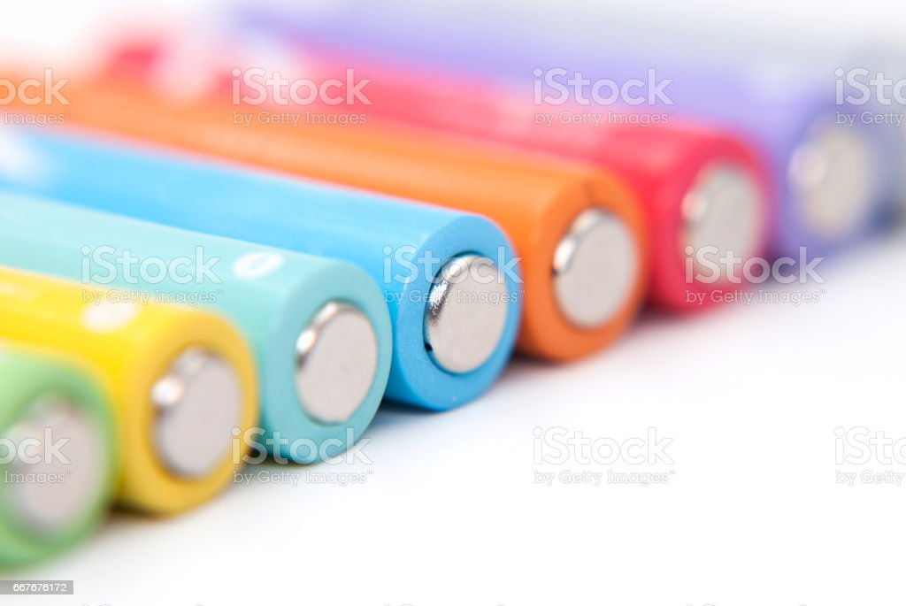 Several AA batteries in perspective closeup view on white background stock photo