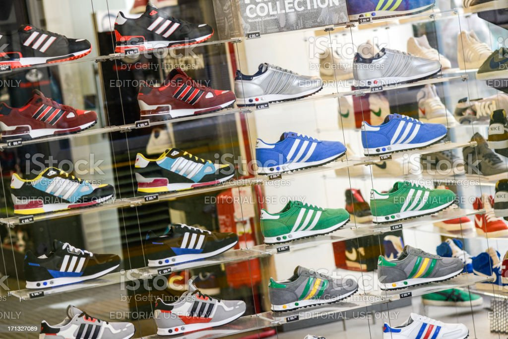 Several Adidas shoes in Foot Locker store window stock photo