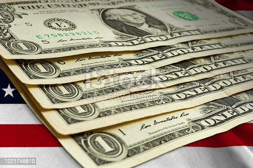 Several American dollar bills lie on the background of the US national flag. Cash paper money. Currency.